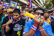 "14 JANUARY 2014 - BANGKOK, THAILAND:  Anti-government protestors blow horns and whistles in front of Royal Thai Police headquarters. The whistle has emerged as the protestors' main weapon against the government. Hundreds of protestors picketed police headquarters because they accuse the police of siding with the government during the protests. Tens of thousands of Thai anti-government protestors continued to block the streets of Bangkok Tuesday to shut down the Thai capitol. The protest, ""Shutdown Bangkok,"" is expected to last at least a week. Shutdown Bangkok is organized by People's Democratic Reform Committee (PRDC). It's a continuation of protests that started in early November. There have been shootings almost every night at different protests sites around Bangkok, but so far Shutdown Bangkok has been peaceful. The malls in Bangkok are still open but many other businesses are closed and mass transit is swamped with both protestors and people who had to use mass transit because the roads were blocked.    PHOTO BY JACK KURTZ"