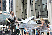 """Arthur Darvill and Joanna Christie, of ONCE, the Tony Award-winning musical, kick off a day of free concerts as part of the celebration of """"Art for All"""" and the conclusion of the Sing for Hope Pianos project, supported by Chobani, Inc., at Lincoln Center, Sunday, June 16, 2013, in New York.  (Photo by Diane Bondareff/Invision for Sing for Hope)"""
