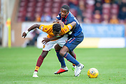 Arnaud Djoum (#10) of Heart of Midlothian fouls Andy Rose (#15) of Motherwell FC during the Ladbrokes Scottish Premiership match between Motherwell and Heart of Midlothian at Fir Park, Motherwell, Scotland on 15 September 2018.