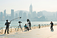 Tourists and film set statues with Hong Kong Island Victoria Harbour behind. On the Avenue of Stars promenade, Kowloon, China