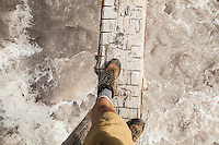 A first person view of legs and feet as a person crosses a log bridge over the Carbon River, Mount Rainier National Park, Washington, USA.