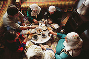 Çinar family share a breakfast of tea, tomatoes, spiced meat, bread, feta cheese, olives, sugar, butter, and rose jam. The eat sitting on the floor of their living room in their small house in Golden Horn area, Istanbul, Turkey. Food, Meal..
