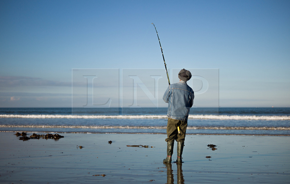 © Licensed to London News Pictures. <br /> 12/10/2014. <br /> <br /> Saltburn, United Kingdom<br /> <br /> Tony Savage, a fisherman from Marske watches his line during the annual Jim Maidens memorial beach fishing competition in Saltburn by the Sea in Cleveland. <br /> The competition is held each year to mark the death of Saltburn plumber and keen fisherman Jim Maidens who died in 1998 when he was killed after being swept overboard from his boat 'Corina' close to the beach at Saltburn.<br /> <br /> Photo credit : Ian Forsyth/LNP