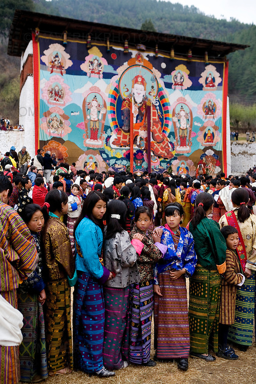 People queue to get blessed by monks at the unveiling of the Thangka (religious mural) of Guru Rinpoche in the final event of the Paro festival at Rinpung dzong, Paro..Commonly described as the last Himalayan Shangrila, Bhutan is a country of unique serenity, harmony, and beauty. Nestled between India, China, and Tibet, this independent country whose name translates as 'the Land of the Thunder Dragon' has for the past 300 years  proactively followed a policy of isolation and cultural protection. Travel in and out of the country is strictly regulated, and the impact of outside influences on the local culture is carefully monitored. Spirituality is an important aspect of Bhutanese culture, with Buddhism being interlinked with everyday life. Gross National Happiness (GNH), as opposed to GNP/GDP, forms the cornerstone of its development strategy which focuses on a holistic development strategy that complements its cultural and Buddhist spiritual values.