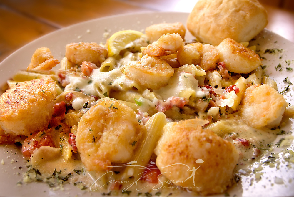 A shrimp and scallops pasta dish is pictured at Sunset Grille, March 19, 2016, in St. Augustine, Florida. The dish features shrimp and scallops sautéed with garlic, white wine, pesto, bacon, mushrooms, tomatoes, scallions and parsley, tossed with mozzarella, Parmesan and a touch of cream over penne pasta. The restaurant opened in 1990 and offers a laidback, Key West atmosphere. (Photo by Carmen K. Sisson/Cloudybright)