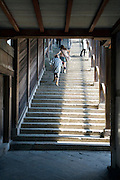 some young adult girls running up long stairs at the end of a corridor at the Todai-ji Nigatsu-do temple Japan Nara