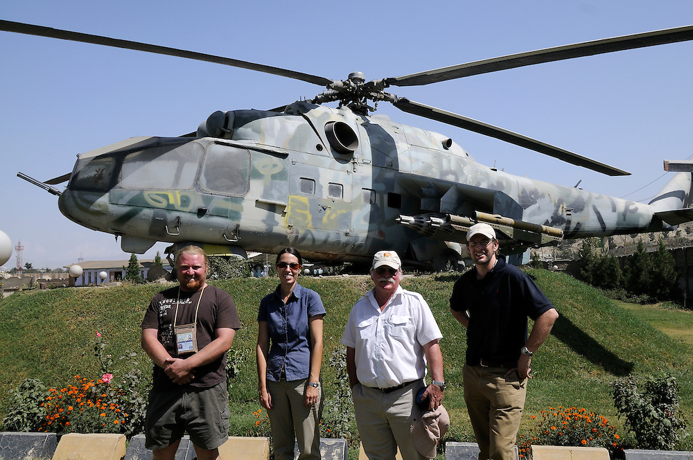 "Pilot, Danielle Aitchison, stands in front of a Russian Helicopter with UNHAS colleagues at the OMAR Landmine Museum in Kabul.  Danielle flies in Afghanistan for The United Nations Humanitarian Air Service (UNHAS).   Left to right:  Engineer Mauritz Groenewald, Danielle, Base Manager Dave Findlay, Pilot Chris Hood....When asked about flying in a war zone, she says,  ""I'm just a normal average female.  My job is maybe a little different to some, but I have the same feminine side as other women.  I don't have any trouble going back to New Zealand relating to people.  I'm just a regular chick.""."