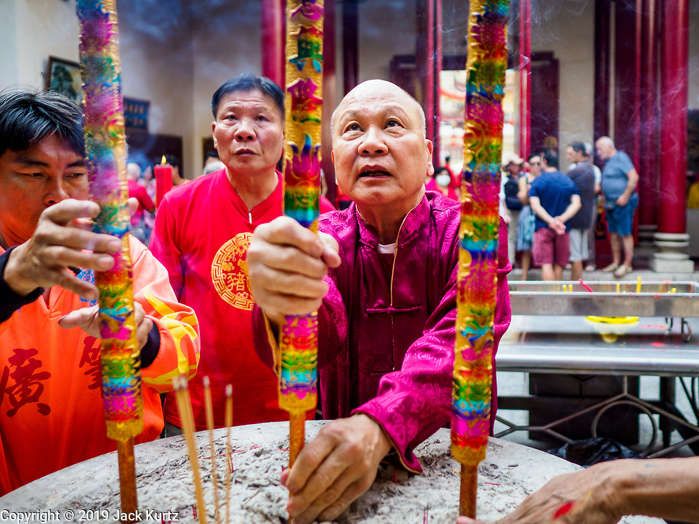 05 FEBRUARY 2019 - BANGKOK, THAILAND:  A man places incense sticks in a pot at Canton Shrine in Bangkok during Chinese New Year observances. Chinese New Year celebrations in Bangkok started on February 4, 2019, although the city's official celebration is February 5 - 6. The coming year will be the Year of the Pig in the Chinese zodiac. About 14% of Thais are of Chinese ancestry and Lunar New Year, also called Chinese New Year or Tet is widely celebrated in Chinese communities in Thailand.     PHOTO BY JACK KURTZ