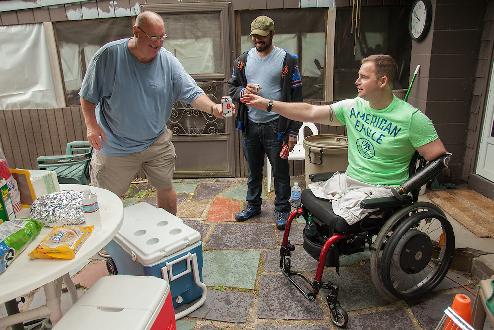 Injured Air Force Master Sgt. Joseph Deslauriers Jr. is handed a beer by his father, Joseph Sr., during a cookout at his boyhood home in Bellingham, MA on Sunday, May 19, 2013. Deslauriers' high school friend Derrick Floyd (C) is also pictured. In 2011, Deslauriers lost both of his legs and part of an arm after stepping on an explosive device while stationed in Afghanistan. He is currently rehabbing at Walter Reed Army Medical Center.  (Matthew Cavanaugh for The Washington Post)