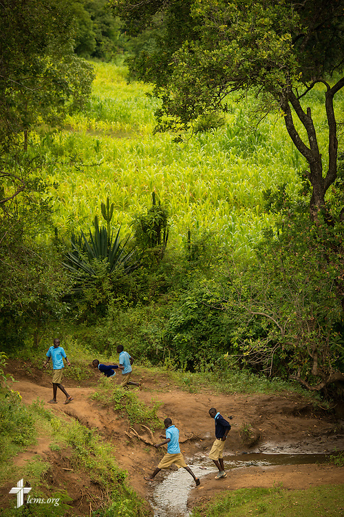 Students from a nearby school cross a small creek near the U-Dom ELCK (Evangelical Lutheran Church in Kenya) Project 24 site on Thursday, June 23, 2016, in Chepareria, Kenya.  LCMS Communications/Erik M. Lunsford