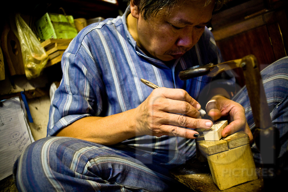 A Vietnamese man carves out handmade stamps in his home on Ta Hien street in the Old Quarter of Hanoi, Vietnam, Southeast Asia