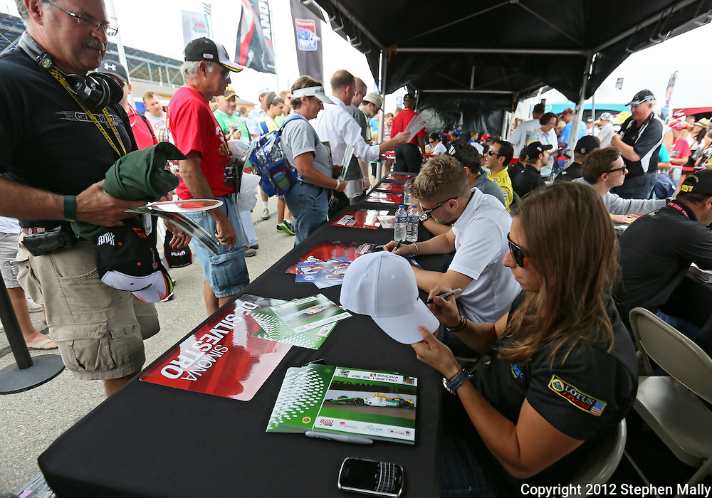 Simona De Silvestro signs autographs before the start of the IZOD IndyCar Iowa Corn Indy 250 auto race at the Iowa Speedway in Newton, Iowa on Saturday, June 23, 2012.