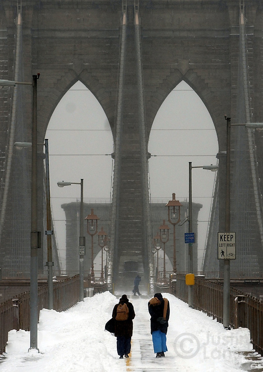 Pedestrians are seen on the snowy Brooklyn Bridge following a major winter storm in Brooklyn, NY Sunday, 23 January 2005. The storm dumped over a foot of snow, up to three in some places, on the Eastern United States, causing nearly 500 flights to be canceled Sunday morning at the New York metropolitan area's Newark, Kennedy and LaGuardia airports.