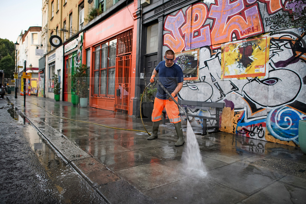 © Licensed to London News Pictures. 27/08/2019. London, UK. A worker jet washes the pavements in a street in Notting Hill, west London, in the aftermath of the 2019 Notting Hill carnival. The two day event is the second largest street festival in the world after the Rio Carnival in Brazil, attracting over 1 million people to the streets of West London. Photo credit: Ben Cawthra/LNP