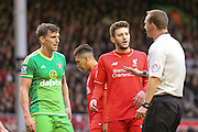 Referee Madley has a word with Sunderland defender Billy Jones  and Liverpool midfielder Adam Lallana  during the Barclays Premier League match between Liverpool and Sunderland at Anfield, Liverpool, England on 6 February 2016. Photo by Simon Davies.