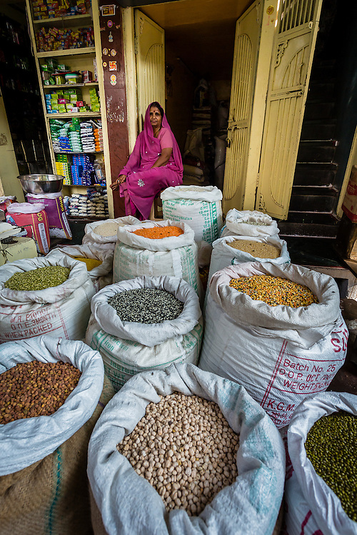 A woman stands in her grain stall, near all the sacks of grain and beans she is selling.