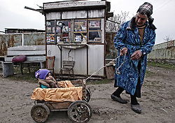 A Georgian old woman with her granddaughter in a cart walks in front of the village's store in Shindishi (20 km from Tbilisi), Saturday 27 March 2004. Parliamentary election will be held in Georgia on Sunday, 28 March 2004.