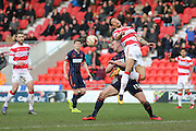 Blackpool defender Tom Aldred (15)  stops Doncaster Rovers forward Nathan Tyson (14)  during the Sky Bet League 1 match between Doncaster Rovers and Blackpool at the Keepmoat Stadium, Doncaster, England on 28 March 2016. Photo by Simon Davies.