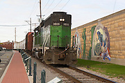 "Cape Girardeau, Missouri MO USA, A train running along the flood-wall with a series of wall paintings on it called ""Mississippi river tales"" at Cape Girardeau, MO."