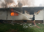 A firefighter battles a blaze with a firehose and uses it to spary water on a burning house.