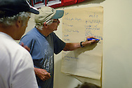 Greg Rivard (left) watches Mike Longmoore write a suggestion for the curriculum of the new Peoples School launched at the windsor Workers Action Centre.