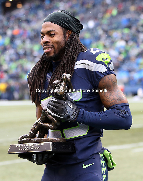 Seattle Seahawks cornerback Richard Sherman (25) receives the Steve largest Award before the 2015 NFL week 16 regular season football game against the St. Louis Rams on Sunday, Dec. 27, 2015 in Seattle. The Rams won the game 23-17. (©Paul Anthony Spinelli)