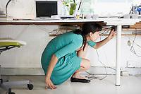Businesswoman Adjusting Cables Under Desk