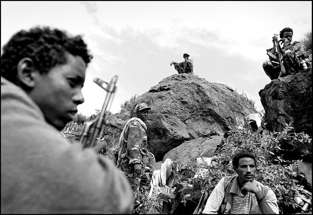 Eritrean soldiers at the  Adi-Quala area of Eritrea, 50 miles from the capital Asmara. Eritrea repulsed the Ethiopian attack in this area despite massive territorial loses elsewhere in the country. Up to 1 million people were displaced and over 100,000 people killed in the 2-year border war between Eritrea and Ethiopia. ....An Ethiopian soldier lies buried after a failed attack on the Eritrean front lines at Tsorona, Eritrea during the border war between the countries. Over 10,000 Ethiopians were believed killed after this particular failed offensive.