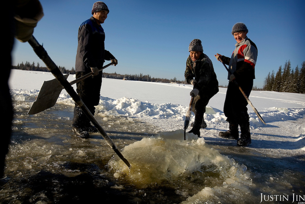 Workers, all members of the United Russia Party, collect ice from a lake near the Bedime village in Yakutia. There is no running water in the 600-strong village, and the ice will be transported to the village to be melted for water. .Nikifor Alfonski, head of the village, is pushing fellow villagers to join the party, which backs Russian President Vladimir Putin. .On one single day this year, 136 people in his village joined the party. .United Russia is a political party in the Russian Federation which usually labels itself centrist. It can be seen as Putin's vehicle in the State Duma (the lower house of Russian parliament). It was founded in April 2001 as a merger between Yuriy Luzhkov's, Yevgeny Primakov's and Mintimer Shaeymiev's Fatherland - All Russia party, and the Unity Party of Russia, led by Sergei Shoigu and Alexander Karelin..United Russia is a relatively new party in the Russian Parliament but has been making great gains in recent federal and local elections due to the popularity of Putin.