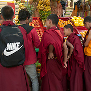 India. Bihar. Bodhgaya, the town where the Buddha sat under a sacred fig tree (bhodi tree) and received enlightenment. Young Buddhist monks buy fruit.