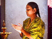 05 JUNE 2015 - KUALA LUMPUR, MALAYSIA:   A woman prays in Sri Mahamariamman Temple, the oldest functioning and most important Hindu temple in Malaysia. The principal deity in the temple is Mariamman,  a deity that is popularly worshipped by overseas Indians, especially Tamils, because she is looked upon as their protector during the sojourn to foreign lands. Mariamman is a manifestation of the goddess Parvati, an incarnation embodying Mother Earth with all her terrifying force. She is associated with disease and fever and protects her devotees from unholy or demonic events.    PHOTO BY JACK KURTZ
