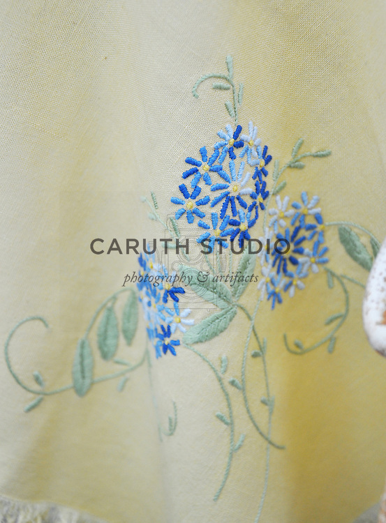 Vintage garden: Detail of embroidered tablecloth inside glass shed