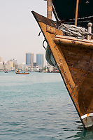 Dubai UAE old wooden dhow docked on Dubai Creek Rolex Towers of Deira in distance