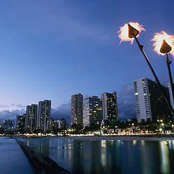Tiki torches light up as the sunsets on the Waikiki strip on the island of Oahu, Hawaii.