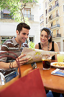 Young couple at cafe reading map together portrait