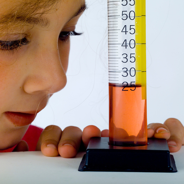 Volumes of liquid being measured by a girl in a graduated cylinder.