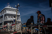 Longshoremen wait for passengers and goods to be shipped each day in the Santana port, one of the preferred scouting places for river pirates, who try to get a sense of valuable goods being moved, a few miles from the capital Macapa, in Amapa state, Brazil, Thursday, Oct. 20, 2016. Bathed by the Amazon river mouth  this northernmost capital of 400.000 residents is as filled with canals, informal docks and unregistered boats as it lacks infrastructure and control means for fighting the rising river piracy plaguing passengers and transportation companies. (Dado Galdieri for The New York Times)