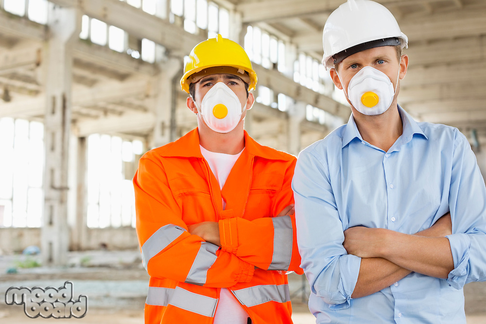 Portrait of confident male construction workers in protective workwear at site
