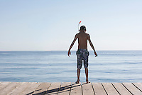 Boy (10-12) standing on jetty in snorkelling mask back view