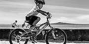 Boy on bicycle, Rangitoto Island behind. Mission Bay, Auckland, New Zealand.