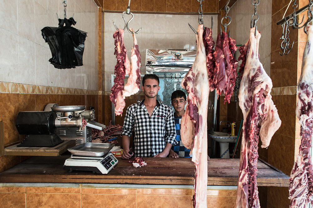 "20-year-old Mahmud Mustafa (l), together with his 16 year old employee Ahmad Ali (r), is standing behind the desk of his butcher store in Kobane. Mahmud has a flock of 200 sheep in a village near Kobane. At the beginning of the fights, he remained there, helped the ""People's Defense Units"" (YPG) fighters slaughtering animals and supplied them with meat for free, Mahmud tells. Then he fled to Turkey with his sheep and returned to Kobane 4 months ago. A kilo of mutton costs 2000 Syrian pounds and it is too expensive for the people and they prefer to buy chicken, Mahmud says. Kobanê (Ayn al-Arab), Syria, June 22, 2015"