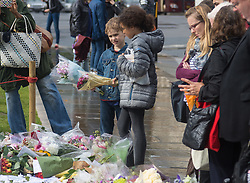 Parliament Square, Westminster, London, June 17th 2016. Following the murder of Jo Cox MP friends and members of the public lay flowers, light candles and leave notes of condolence and love in Parliament Square, opposite the House of Commons. PICTURED: Two children with bouquets look at the hundreds of tributes.
