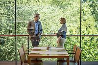 Österreich, Geschäftsmann und Geschäftsfrau vor Restaurant, Kaffeepause, nach dem Meeting, informelle Konversation, entspannte Atmosphäre, Blickrichtung von innen nach außen