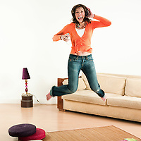 happy woman jumping in a living room listening music