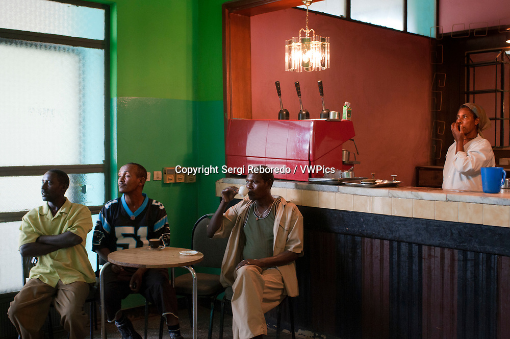 Lake Tana, Bahir Dar, Ethiopia. Interior of a restaurant. The men kill the hours next to an old television. The injera is the typical dish and is found in any restaurant, bar and in all the houses. The injera is the Ethiopian bread. It has a very characteristic and special sour taste. It is made with teff flour (the teff is a local cereal - without gluten - of very small grains, which is very difficult to find outside Ethiopia). The injera is shaped like a large French crêpe.