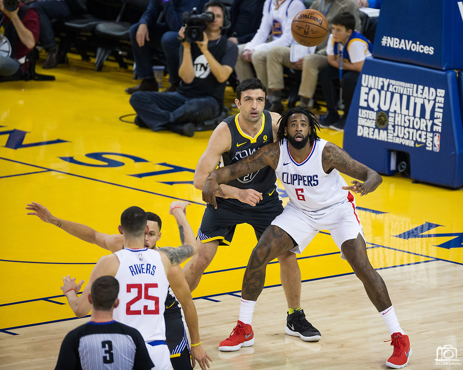 Golden State Warriors center Zaza Pachulia (27) defends LA Clippers center DeAndre Jordan (6) on the block at Oracle Arena in Oakland, California, on February 22, 2018. (Stan Olszewski/Special to S.F. Examiner)