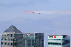 © Licensed to London News Pictures. 10/05/2015.  Today's VE Day anniversary flypast over London as seen from Greenwich. The Red Arrows were seen swooping over London leaving a plume of coloured smoke. Pictured: Red arrows in formation above Canary Wharf.  Credit : Rob Powell/LNP