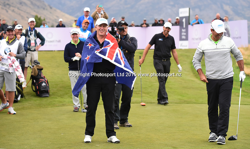 New Zealand Prime Minister John Key wears the New Zealand flag after Ricky Ponting pulls out the New Zealand flag on the first tee during the ANZ Challenge and round 4 at The Hills during 2016 BMW ISPS Handa New Zealand Open. Sunday 13 March 2016. Arrowtown, New Zealand. Copyright photo: Andrew Cornaga / www.photosport.nz