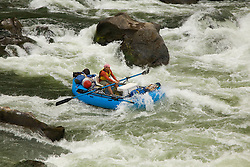 United States, Oregon, Rogue River, man rowing whitewater raft through rapids.  MR