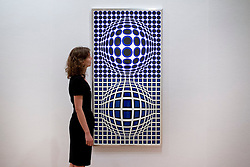 © Licensed to London News Pictures. 08/10/2012. LONDON, UK. A member of Bonhams staff views Victor Vasarely's 'Oltar-BMB' (1972) (est. GB£50,000-80,000) ahead of a sale at the auction house's New Bond Street premises. The auction, featuring a collection of contemporary art and design is set to take place on Thursday the 11th of October at Bonham's New Bond Street auction house. Photo credit: Matt Cetti-Roberts/LNP